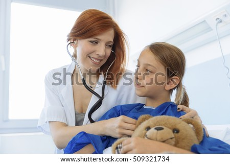 Female doctor examining child patient in hospital