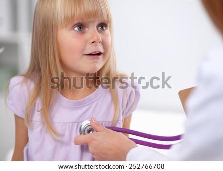Female doctor examining child with stethoscope at surgery,isolated - stock photo
