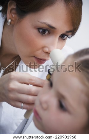 Female doctor examining girl's ear - stock photo