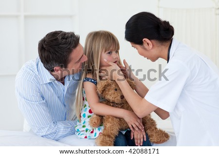 Female doctor examining little girl accompanied by her father - stock photo