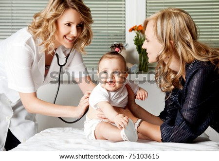 Female doctor examining little smiling baby girl, held by mother - stock photo