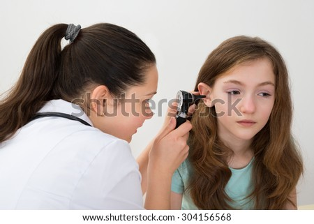 Female Doctor Examining Patient Ear With Otoscope In Clinic - stock photo