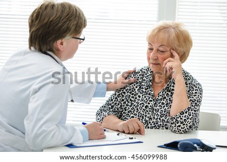 Female doctor explaining diagnosis to her senior patient - stock photo