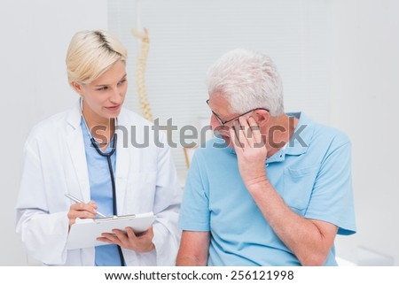 Female doctor explaining prescription to senior male patient in clinic - stock photo