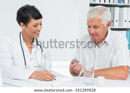 Female doctor explaining reports to male patient at medical office - stock photo