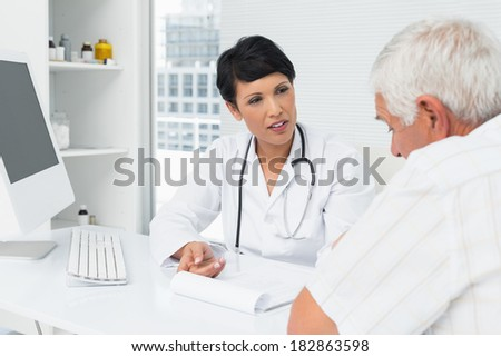 Female doctor explaining reports to senior patient at medical office - stock photo