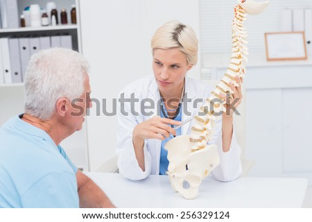 Female doctor explaning spine model to senior male patient in clinic - stock photo