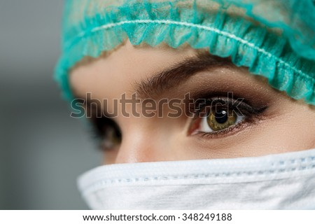 Female doctor face wearing protective mask and green surgeon cap closeup. Nurse eyes close up gazing intently. Resuscitation, emergency, save patient life, surgery, medical help and insurance concept - stock photo