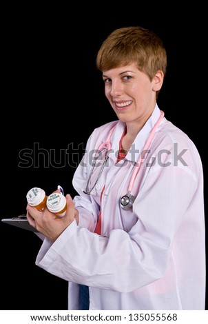 Female doctor filling out paperwork on a clipboard. Shot on a black background. - stock photo