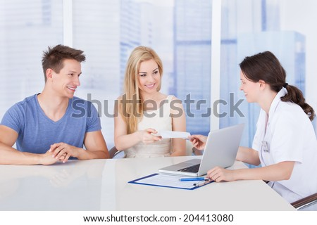 Female doctor giving prescription paper to young couple at desk in clinic