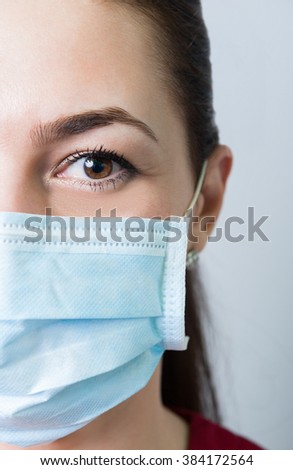 Female doctor half face or medical concept on gray background - stock photo