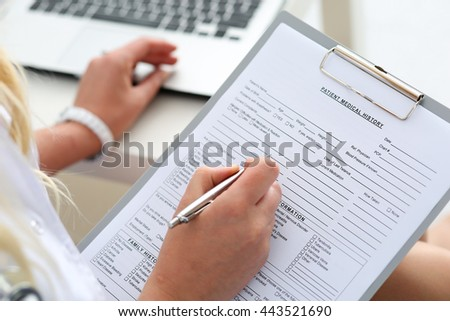 Female doctor hold clipboard pad and fill medical history list with silver pen. Physical, disease prevention, 911, prescribe remedy, ward round, therapeutist assistance, healthy lifestyle concept - stock photo