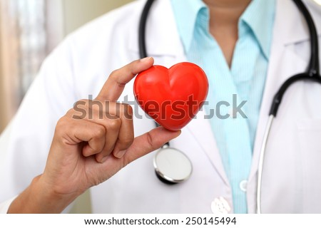 Female doctor holding a beautiful red heart shape  - stock photo