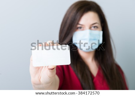 Female doctor holding a blank contact card or paper with copy space and advertising area - stock photo