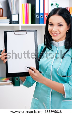 Female doctor holding a clipboard at the workplace - stock photo