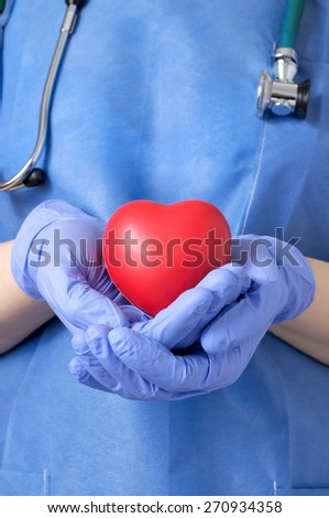 Female doctor holding a red heart shape - stock photo