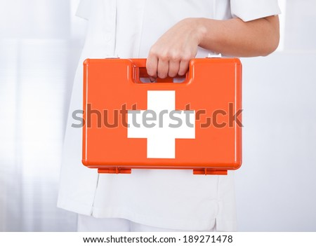 Female doctor holding first aid box in hospital - stock photo