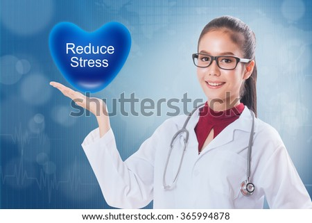 Female doctor holding heart with reduce stress sign on medical background.
