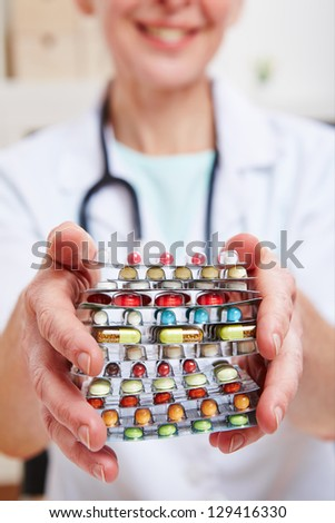 Female doctor holding many colorful pills in her hands - stock photo
