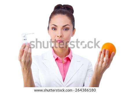 Female doctor holding orange and medicine isolated on white background - stock photo
