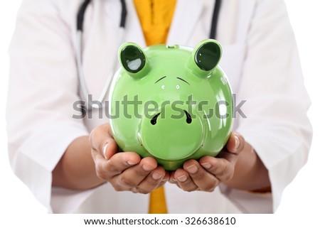 Female doctor holding piggy bank  - stock photo