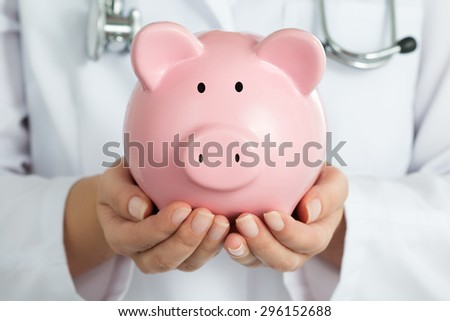 Female Doctor Holding Piggy Bank. Doctor's hands close-up. Medical insurance and health care concept. - stock photo