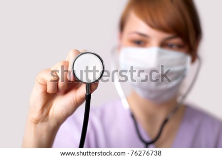 Female doctor holding stethoscope pointed toward camera (selective focus) - stock photo
