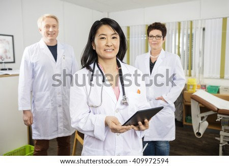 Female Doctor Holding Tablet Computer While Standing With Collea - stock photo