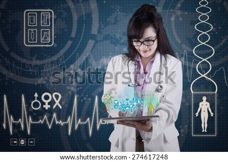 Female doctor holding tablet pc with medical app - stock photo