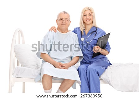 Female doctor hugging a mature patient seated in a hospital bed isolated on white background - stock photo