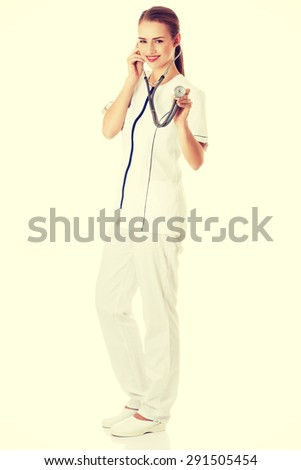 Female doctor in uniform examining by a stethoscope - stock photo