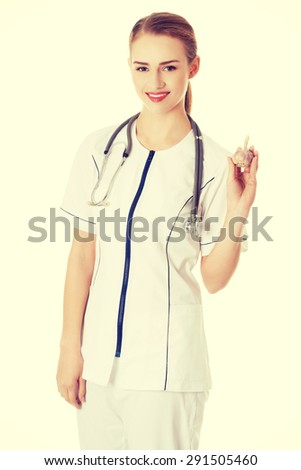 Female doctor in uniform holding garlic - stock photo