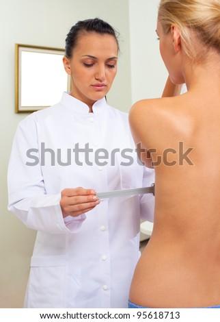 Female doctor in white uniform examine woman breast - stock photo