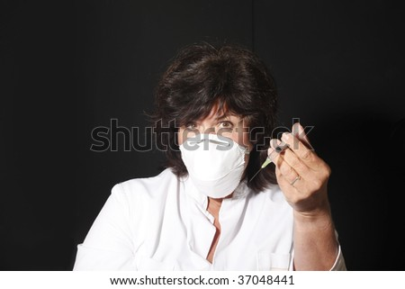 Female doctor insists with syringe that a vaccination is inevitable. - stock photo