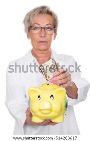 female doctor is putting a dollar note into a  piggy bank, isolated on white