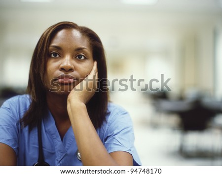 Female doctor leaning on her hand - stock photo