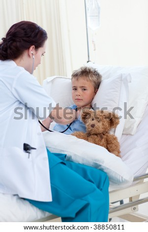 Female doctor listening to a child chest with stethoscope in bed - stock photo