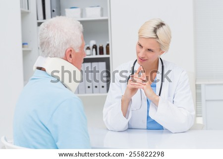 Female doctor looking at senior patient wearing neck brace in clinic
