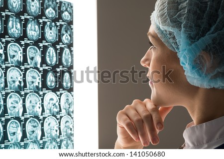 female doctor looking at the x-ray image attached to the glowing screen - stock photo