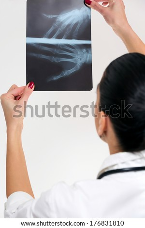 Female doctor, looking X-Ray, isolated on white background.