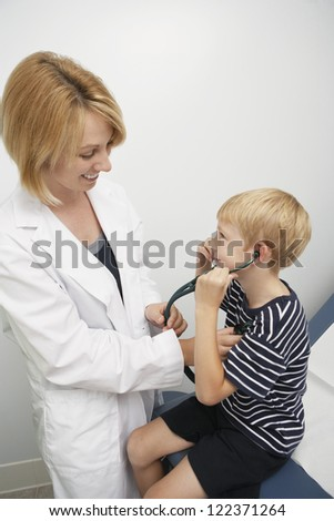 Female doctor making boy listen his heartbeat with stethoscope