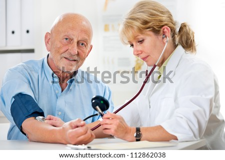 Female doctor measuring blood pressure of senior  man - stock photo