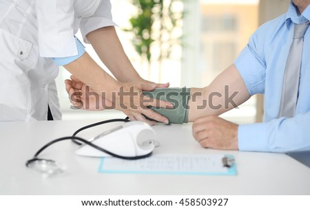 Female doctor measuring man blood pressure with tonometer