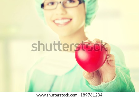 Female doctor or nurse holding heart shaped toy - stock photo