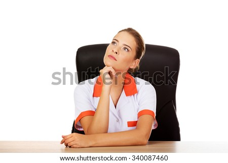 Female doctor or nurse sitting behind the desk. - stock photo
