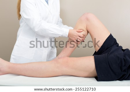 Female doctor physiotherapist practicing massage to her leg male patient in medical center. - stock photo