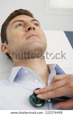 Female doctor's hand checking male patient using stethoscope - stock photo