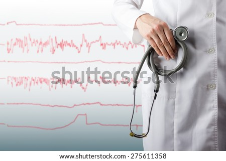 Female doctor's hand holding stethoscope on blurred medical blue background and ecg line. Concept of Healthcare And Medicine. Copy space - stock photo
