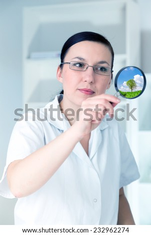 Female doctor scrutiny with a magnifying glass with a surprised expression - stock photo