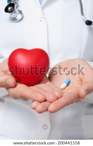 Female doctor showing a red heart and a blue pill - stock photo